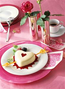 Panna cotta heart with puff pastry arrow on red fruit sauce