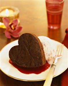 Small heart-shaped chocolate cake with ice cream & fruit sauce