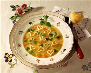 Heart soup with vegetable on plate, heart-shaped roll