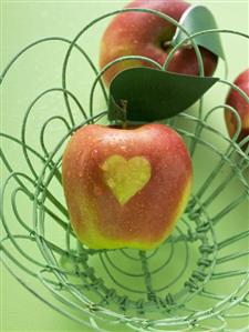 Red apples with heart in and beside wire basket