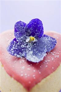 Small heart-shaped cake with pink icing and violet