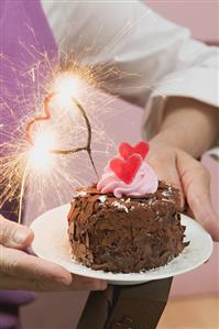 Woman holding small chocolate cake with sparkler