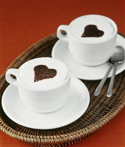 Two cups of cappuccino with hearts
