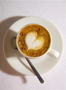 A cup of espresso macchiato with milk foam heart