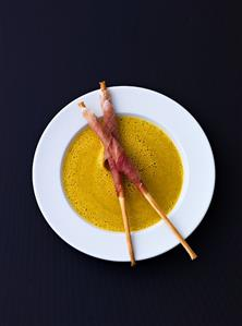 Curried courgette soup, grissini wrapped in prosciutto